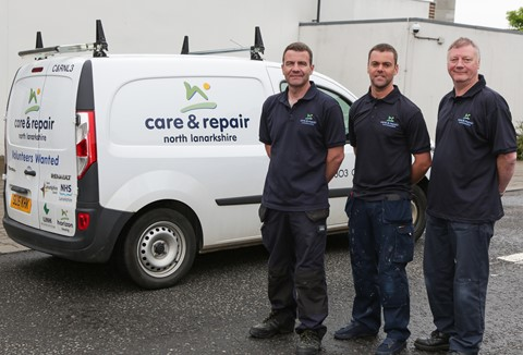 Three man standing next to a care and repair van