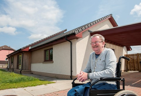 Man in wheelchair outside his house